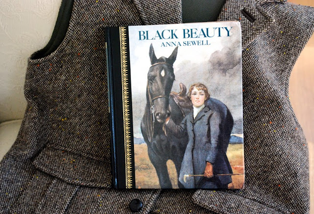 Black Beauty, hardcover book, resting on tweed vest