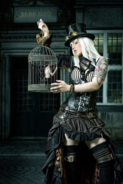 Steamreaper halloween costume: a woman holds a tiny man hostage in a birdcage. She's wearing black steampunk clothing.