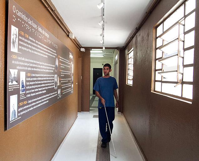 Museu Sensorial: Deficiente visual caminha, com auxílio de uma bengala, em corredor de um edificio , com piso tatil. As paredes são marrons. De um lado do corredor vê-se posteres