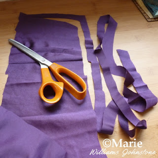 Orange handled fabric scissors cutting a long strip of purple material