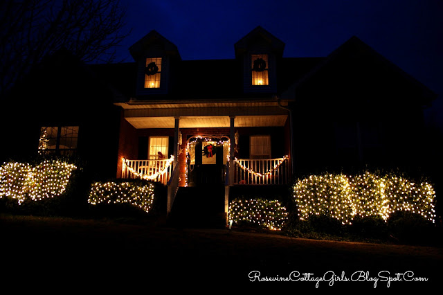 Christmas at the cottage | A cottage at night with white christmas light in the bushes and the porch with windows lit from within. | Rosevinecottagegirls.com