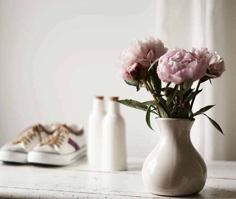 gefüllte Päonien in einer shabby-weißen Vase mit Schuhen und Flaschen im Hintergrund { by it's me! }