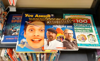 Children's science books lying face-up on library shelf: 'Experimenting with Science in Sports' by Robert Gardner, 'You Asked? Over 300 Great Questions and Astounding Answers' by Katherine Farris, 'MythBusters Science Fair Book' by Samantha Margles and 'More Than 100 Experiments for Science Fairs and Projects' by Vicki Cobb