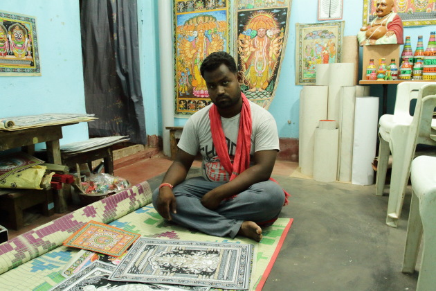 A Raghurajpur artisan showing me his various paintings