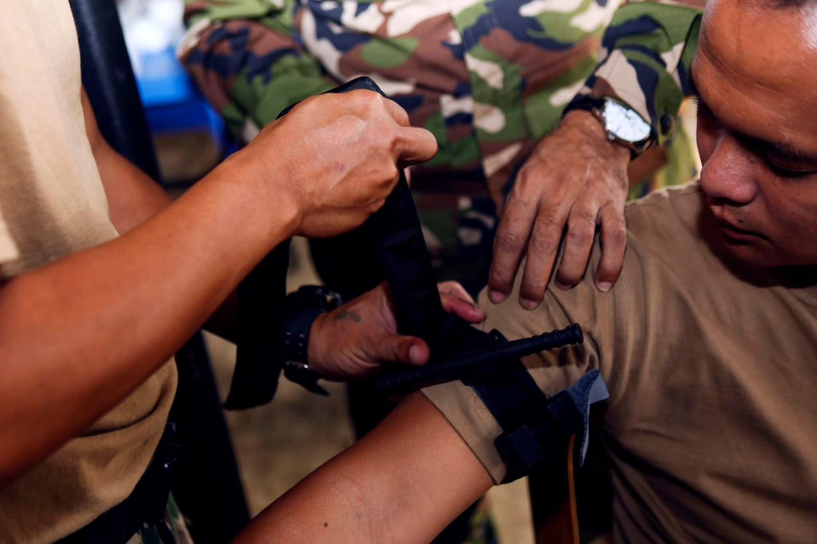 A military member practices putting a tourniquet on the arm of another military member