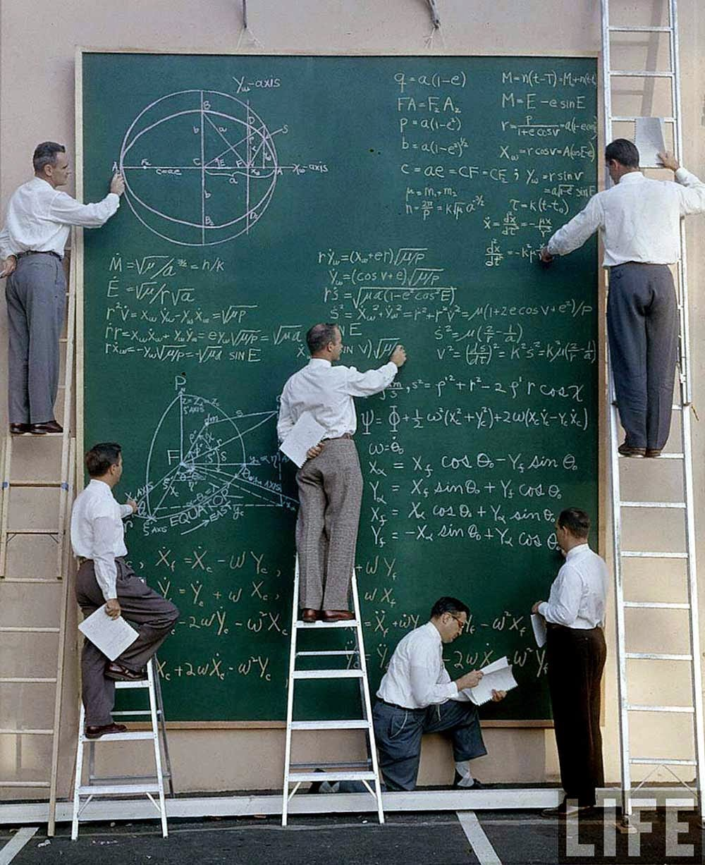 Six unidentified scientists uses a ladders and a large chalk board to work out equations for satellite orbits at Systems Labs, California, 1957.