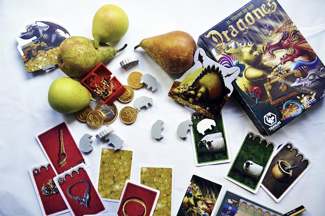 La caja del juego junto a fruta y monedas de chocolate, sus cartas, y ovejas de madera