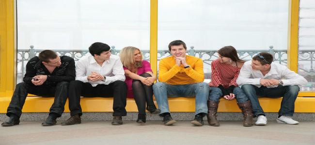 Grupo de jovens reunidos observando o que está centrado no centro