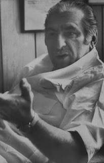 A man of eastern European descent, wearing an open-neck short-sleeve shirt, leaning back in a chair and gesturing as if speaking to a person standing off-camera