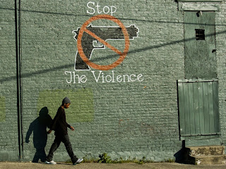 Young man walks past a stop the violence sign on a city building.