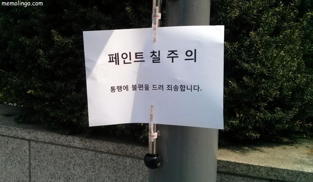 Cartel en coreano adivirtiendo de que una farola está recién pintada