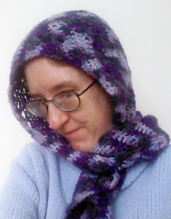 A woman wearing a hood with a scarf.  The hood is done in worsted-weight crochet in a chevron pattern.  The yarn is varigated yarn that runs between purple, black, and grey.