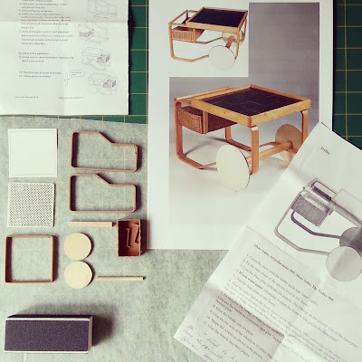 One-twelfth scale miniature kit pieces for an Alvar Aalto trolley 900, laid out with the instruction sheets and a photo of the original for reference.