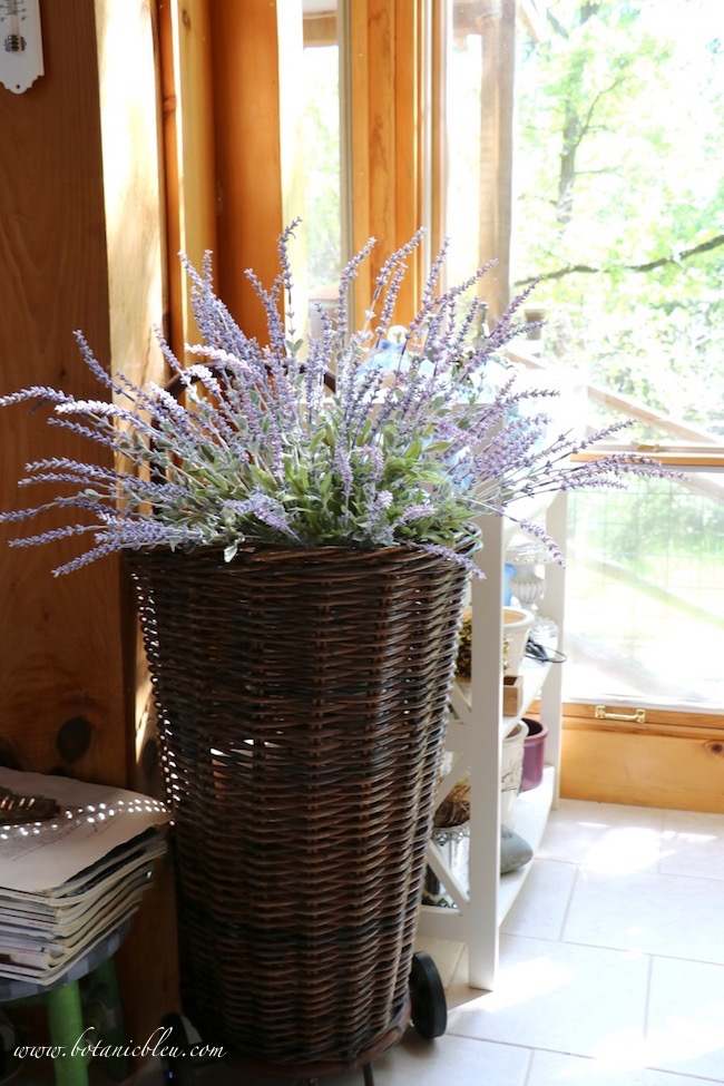 Faux lavender that looks real in a reproduction French market basket provides vintage French style for a French-inspired home