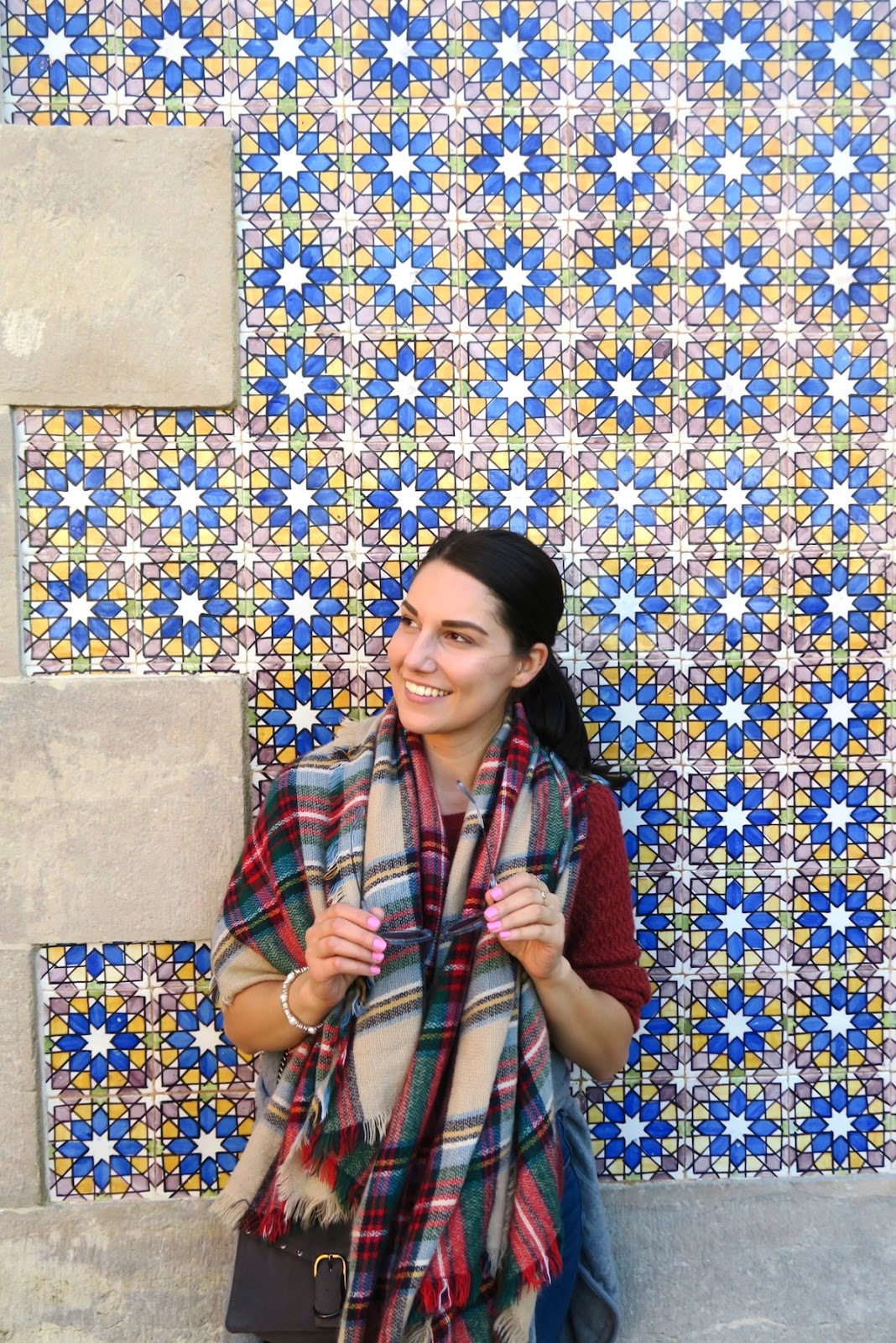 This is a close up of me standing at the Pena Palace with some beautiful tile work behind me. I'm holding my sunglasses and wearing my holiday inspired scarf.