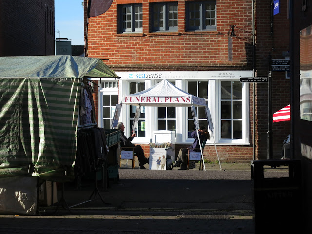 Open-sided tent with two people sitting on chairs and selling funeral plans at Ringwood Market.