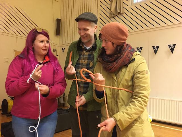 Kolme henkeä opettelee solmujen tekemistä narulla