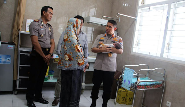 Kapolres Lumajang didampingi Kapolsek Candipuro saat menimang bayi malang itu