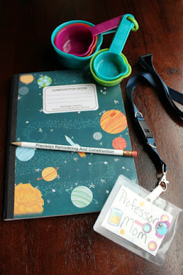 a composition notebook, pencil, name tag and measuring cup for the science kits. not pictured: safety glasses