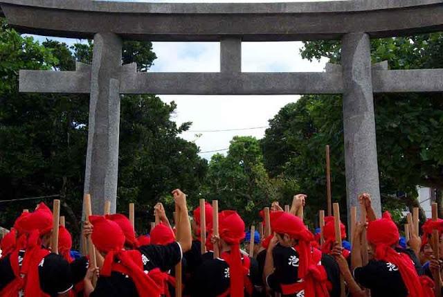 Rituals at Shrine Torii Gate, men with sticks