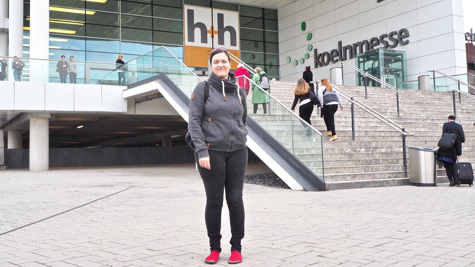 Caros Fuemmeley vor dem Eingang der h+h koelnemsse