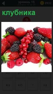 На фотографии изображены ягоды, в том числе лежит среди них клубника и малина