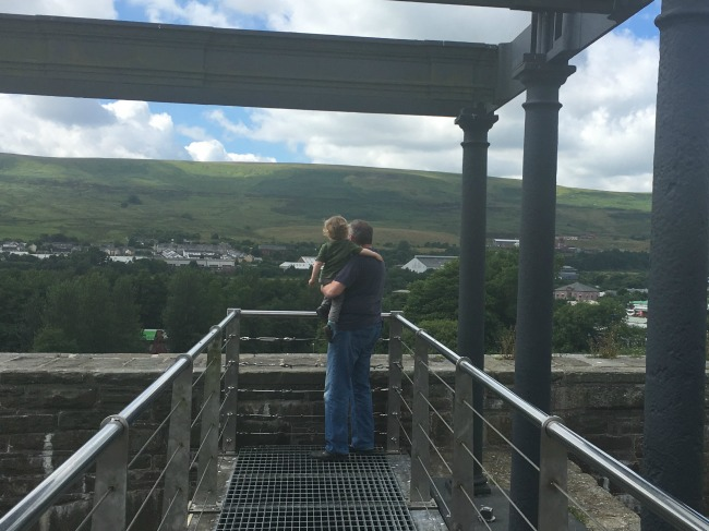 Blaenavon-Ironworks-A-Toddler-and-man-looking-at-the-view-from-the-top-of-the-balance=tower
