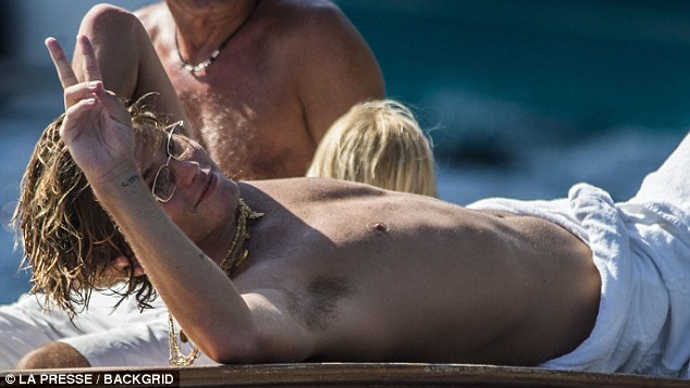 Model Jordan Barrett, 22, has been spotted flaunting his svelte physique alongside US actress Michelle Rodriguez, 40, at the Fontelina Beach Club in Capri on Monday after also recently been snapped partying aboard a luxury yacht in Italy with a slew of celebrities, including Rita Ora, Tahnee Atkinson, and Emily Ratajkowski.