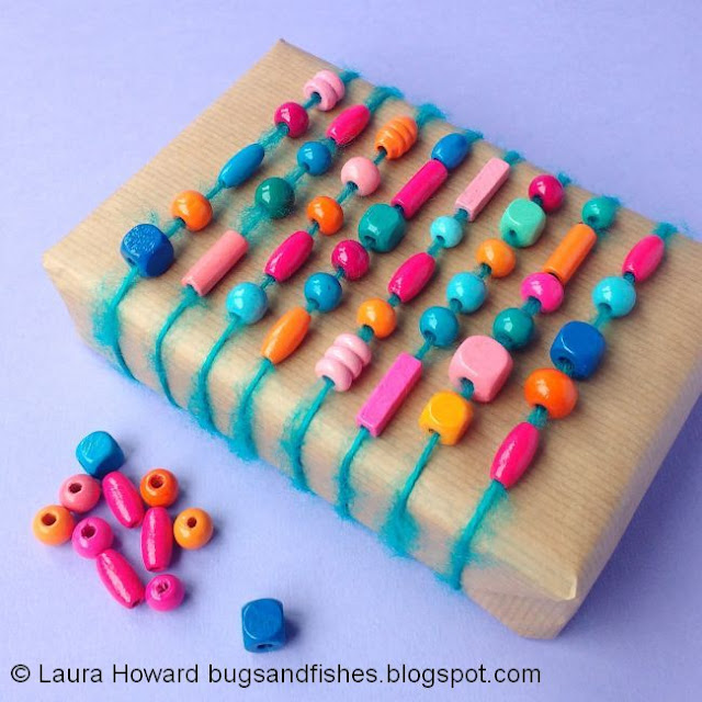A brown paper parcel wrapped with yarn and colourful wooden beads