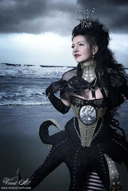 Woman wearing a steampunk victorian octopus corset dress with octopus tentacles, and a crown on her head. Women's steampunk victorian clothing