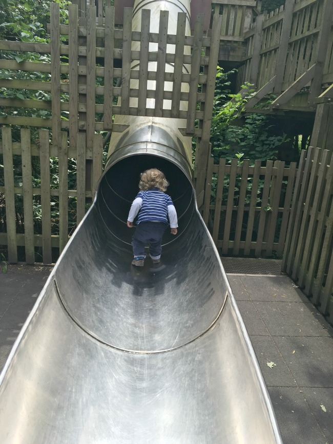 toddler-stood-on-slide-looking-up-at--Perrygrove-Railway-adventure-playground