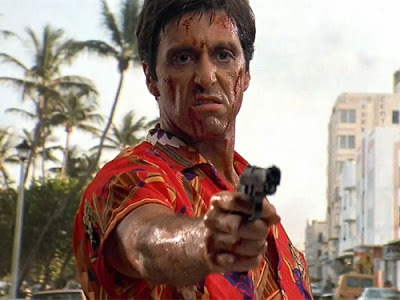 Al Pacino as Tony Montana, covered in blood, holding a revolver, Scarface, Directed by  Brian De Palma