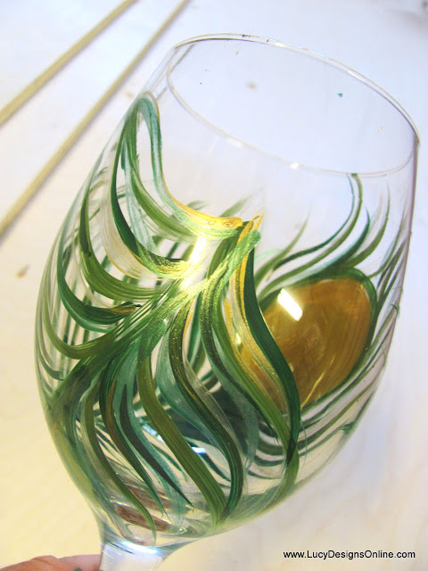 painted wine glass with peacock feather in greens and gold