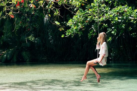 garota pensativa sentada num balanço