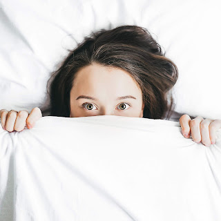 woman in bed with eyes open, alert