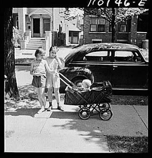 Detroit, Michigan. Little girls wheeling baby brother in a carriage