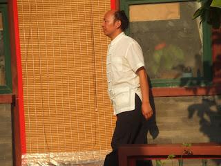 Chinese in weißer Jacke und schwarzer Hose vor brauner Hauswand mit Bambusmatte
