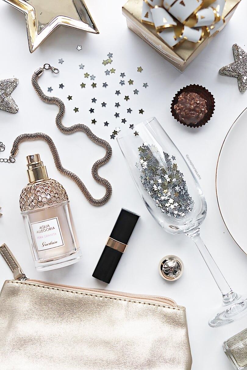 kieliszek do szampana, złota kosmetyczka, biżuteria, perfumy i szminka chanel widok z góry