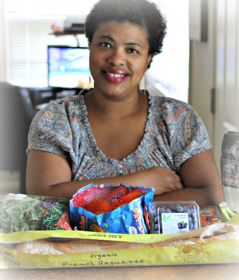 a black woman sitting a table with fruits and veggies