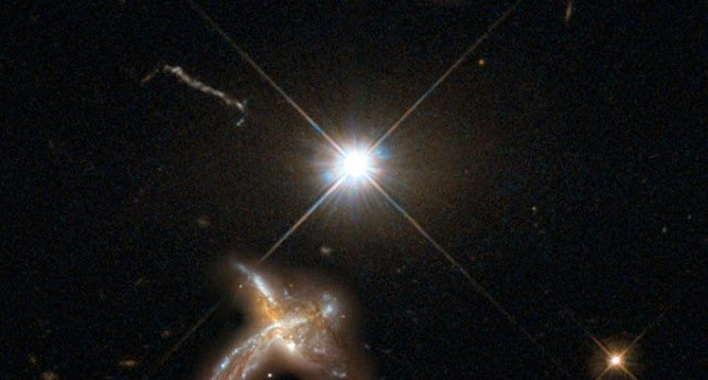 An artist's impression of a quasar and neighboring merging galaxy. The galaxies observed by the team are so distant that no detailed images are possible at present. This combination of images of nearby counterparts gives an impression of how they might look in more detail. The image was created by the Max Planck Institute for Astronomy using material from the NASA/ESA Hubble Space Telescope.