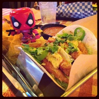 A tiny bobblehead of Deadpool stands in a pile of tortilla chips behind two catfish tacos garnished with remoulade and jalapenos.