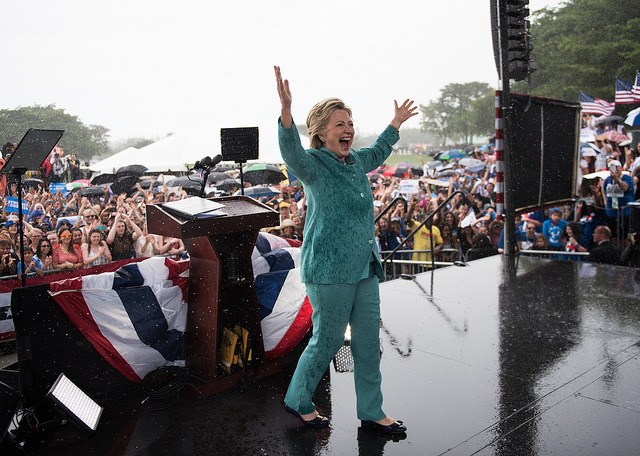 image of Hillary Clinton onstage at the end of an event in Florida, where she'd gotten drenched in a downpour; she has her arms raised above her head in celebration and she is grinning from ear to ear