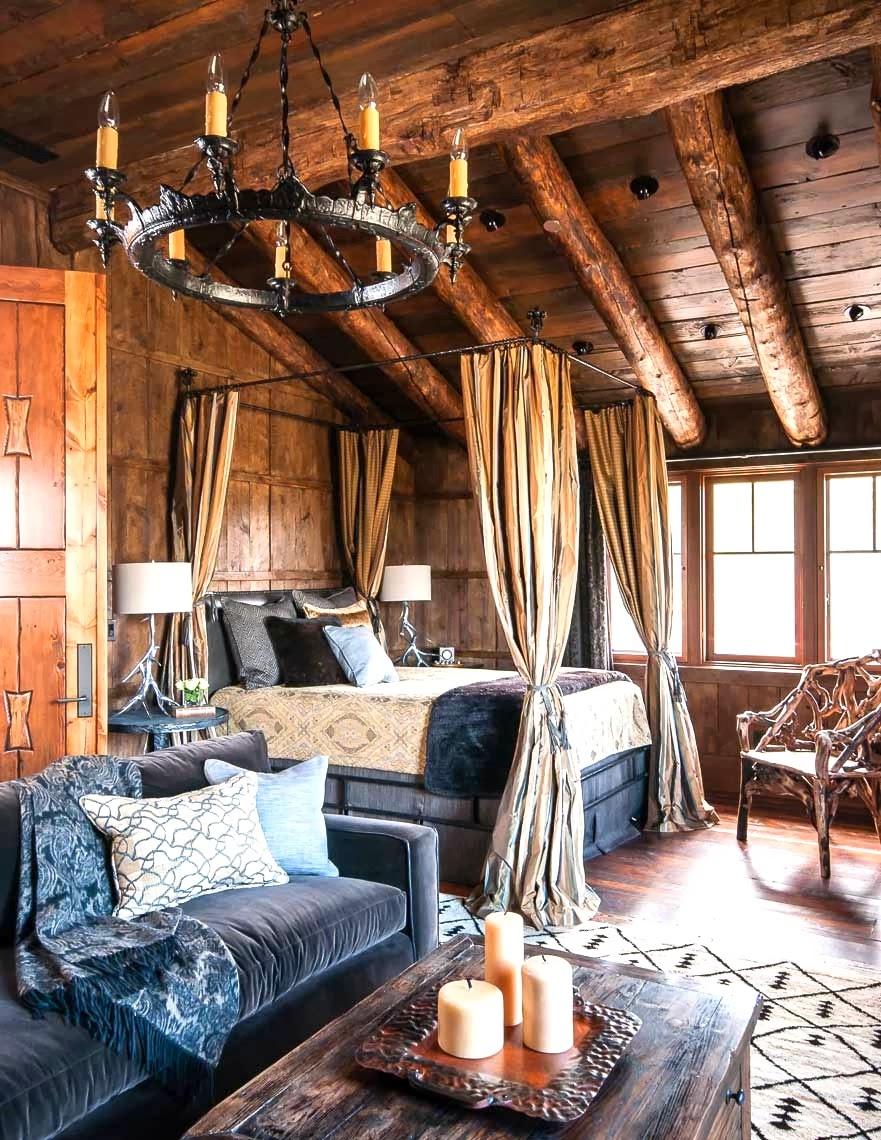 cabin bedroom canopy bed blue velvet sofa iron chandelier rustic log beams cococozy audrey hall