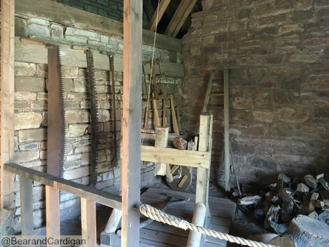 Inside the Reeves cottage. Saws hanging up, logs stacked