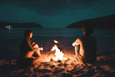 couple-sitting-beside-bonfire