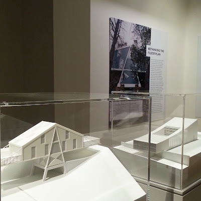Architect's models of two modernist building in perspex cases in front of a large photo and information about one of them on the wall behind.