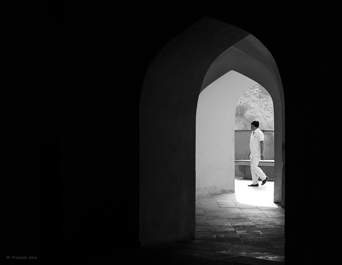 A Black and white Minimalist Photo of a Man dressed in white passing by arcs at Amer Fort Jaipur