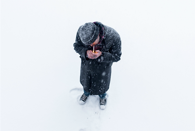 Man trying to light a cigarette, standing in a blizzard