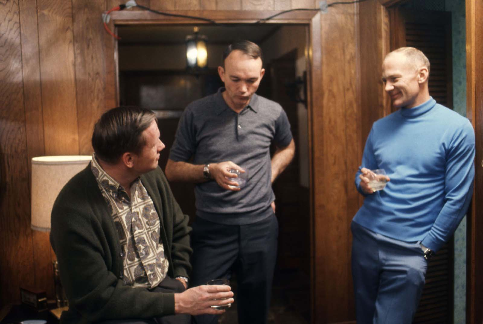 From left: The astronauts Neil Armstrong, Michael Collins, and Buzz Aldrin talk over drinks in a wood-paneled room in Houston, Texas, in March 1969.