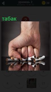 кулаком руки раздавлены сигареты как табак